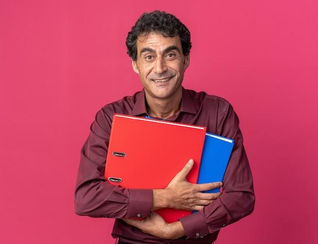 Älterer mann in lila hemd, der ordner hält und die kamera mit einem lächeln auf einem glücklichen gesicht auf rosafarbenem hintergrund anschaut