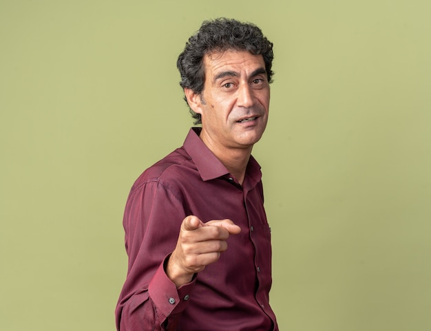 Älterer mann in lila hemd, der selbstbewusst lächelnd mit dem zeigefinger auf die kamera zeigt, die über grün steht