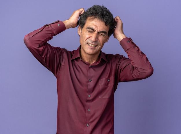 Älterer mann in lila hemd, der verwirrt und sehr ängstlich in die kamera schaut, mit den händen auf dem kopf, die auf blauem hintergrund stehen