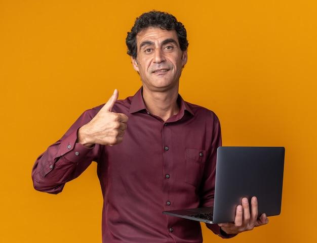 Älterer mann in lila hemd hält laptop mit blick in die kamera und lächelt zuversichtlich und zeigt daumen nach oben über orange