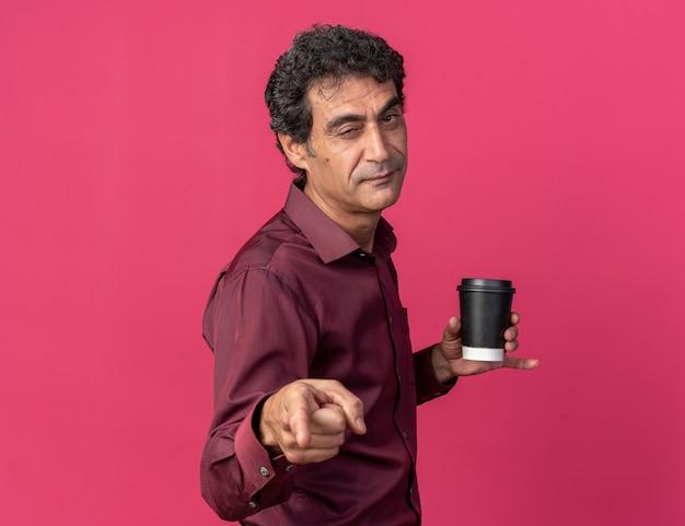 Älterer mann in lila hemd hält pappbecher und zeigt mit dem zeigefinger auf die kamera, lächelt und zwinkert