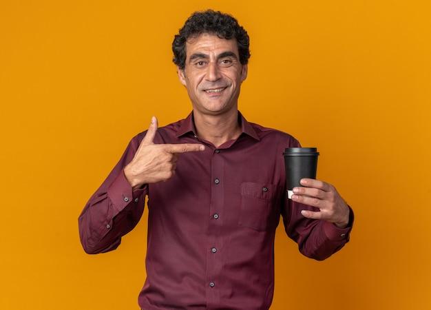 Älterer mann in lila hemd hält pappbecher und zeigt mit dem zeigefinger darauf und lächelt selbstbewusst