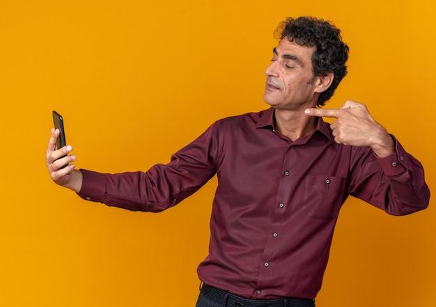 Älterer mann in lila hemd macht selfie mit smartphone und sieht selbstbewusst aus und zeigt mit dem zeigefinger auf den bildschirm, der über orangefarbenem hintergrund steht