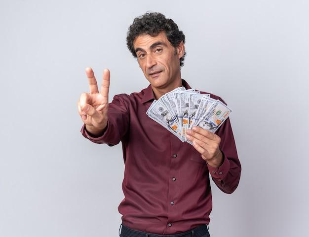 Älterer mann in lila hemd mit bargeld, der glücklich und selbstbewusst in die kamera schaut und ein v-zeichen auf weißem hintergrund zeigt