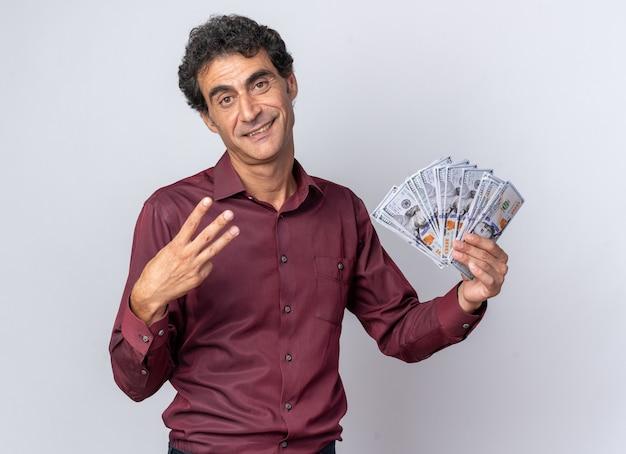 Älterer mann in lila hemd mit bargeld in die kamera schaut glücklich und selbstbewusst mit nummer drei