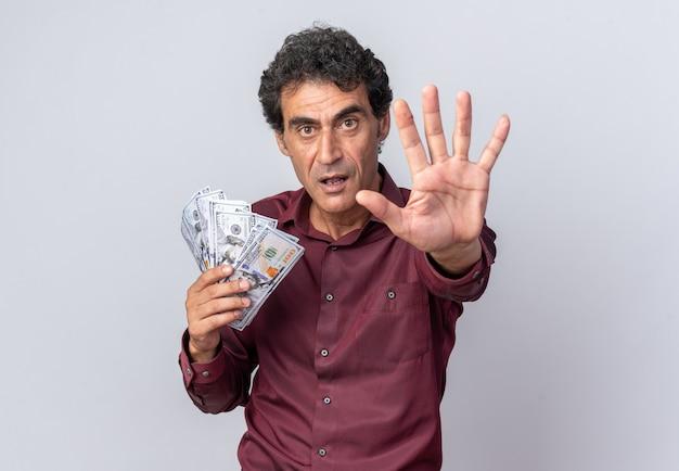 Älterer mann in lila hemd mit bargeld in die kamera schaut mit ernstem gesicht, das stopp-geste macht