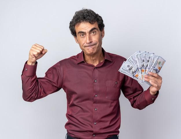 Älterer mann in lila hemd mit bargeld in die kamera schaut mit wütendem gesicht, das faust auf weißem hintergrund zeigt