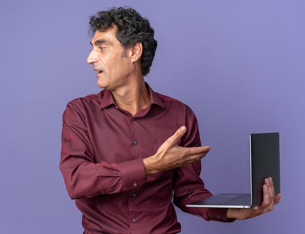 Älterer mann in lila hemd mit laptop, der ihn mit einem handarm präsentiert, der mit einem lächeln auf dem gesicht über blau zur seite schaut