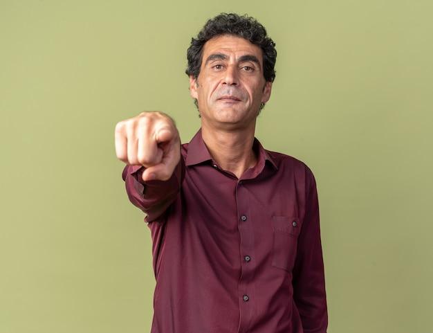 Älterer mann in lila hemd sieht selbstbewusst aus und zeigt mit dem zeigefinger auf die kamera, die über grün steht