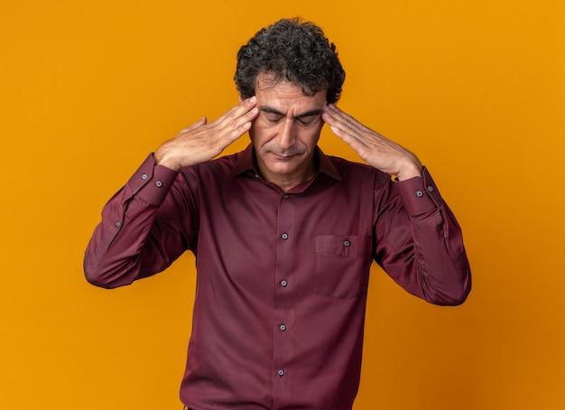 Älterer mann in lila hemd sieht unwohl aus und berührt seinen kopf mit kopfschmerzen