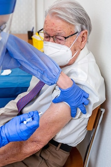 Älterer mann in maske beobachtet, wie krankenschwester in schutzanzug und covid-maske ihm coronavirus-impfstoff gibt