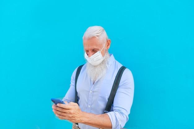 Älterer mann in maske mit modernem telefon während des ausbruchs des coronavirus