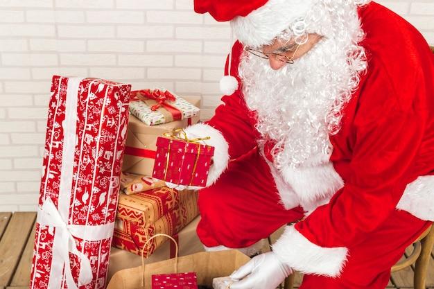 Älterer mann in santa claus-kostüm, das geschenke in kraftbeutel einsetzt
