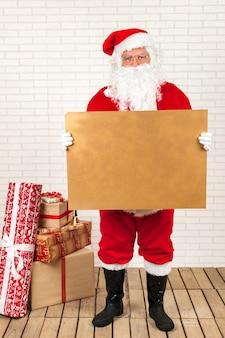 Älterer mann in santa claus-kostüm, das mit leerem papier kraftpapier steht