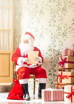 Älterer mann in santa claus-kostüm, das mit wunschliste sitzt