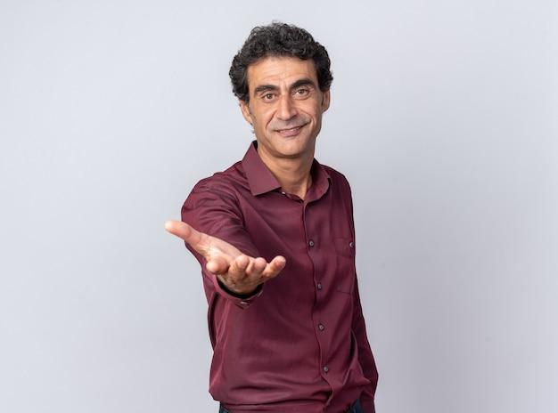 Älterer mann in violettem hemd, der die kamera anschaut, lächelt freundlich und macht hierher geste mit der hand, die über weiß steht Kostenlose Fotos