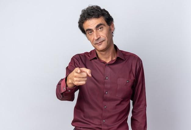 Älterer mann in violettem hemd, der die kamera mit ernstem gesicht ansieht, das mit dem zeigefinger auf die kamera zeigt, die über weißem hintergrund steht