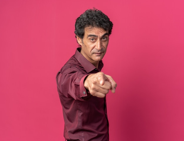 Älterer mann in violettem hemd, der die kamera mit ernstem gesicht betrachtet, das mit dem zeigefinger auf die kamera zeigt, die über rosa steht