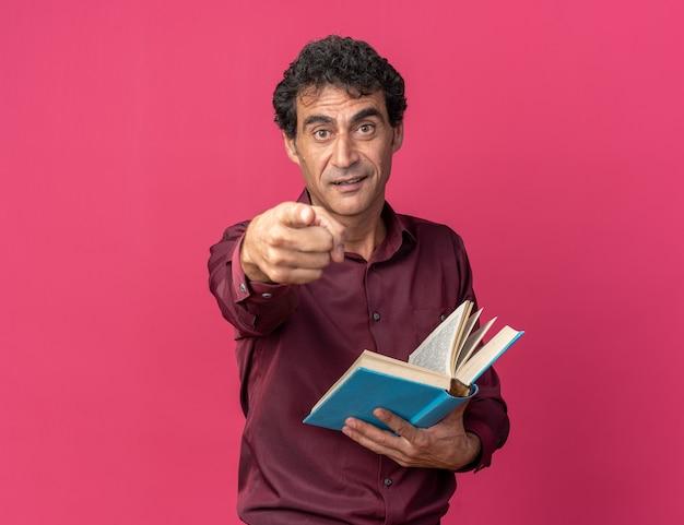 Älterer mann in violettem hemd, der ein offenes buch hält und mit dem zeigefinger auf die kamera zeigt, überrascht über rosa stehend