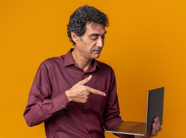 Älterer mann in violettem hemd, der einen laptop hält, der mit dem zeigefinger darauf zeigt, der selbstbewusst über orange steht