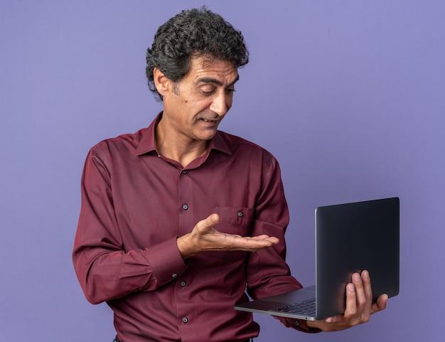 Älterer mann in violettem hemd, der einen laptop hält und mit dem arm auf den bildschirm zeigt, der verwirrt aussieht looking