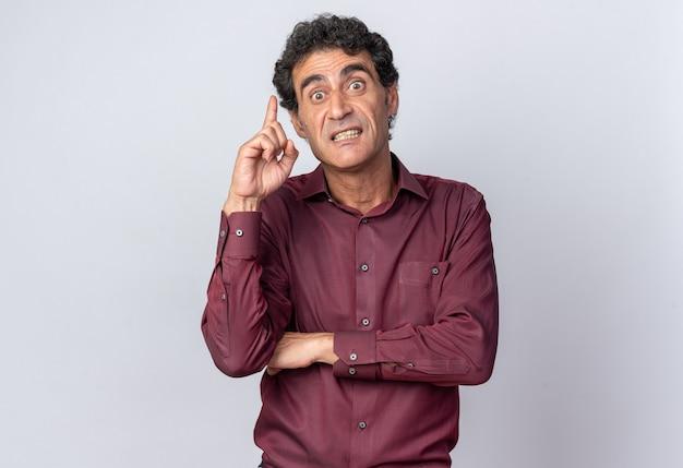 Älterer mann in violettem hemd, der mit wütendem gesicht in die kamera schaut und den zeigefinger zeigt, der über weiß steht