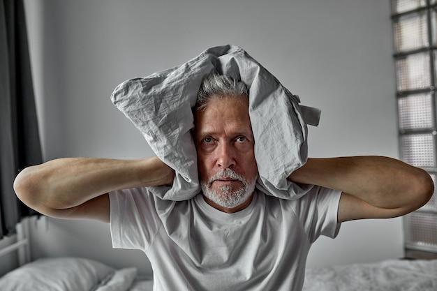 Älterer mann ist es leid, stimmen zu hören, schizophrenie, schließt die ohren mit einer decke, allein zu hause