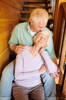 Älterer mann küsste den kopf seiner frau und umarmte sie, während beide zu hause auf einer holztreppe saßen
