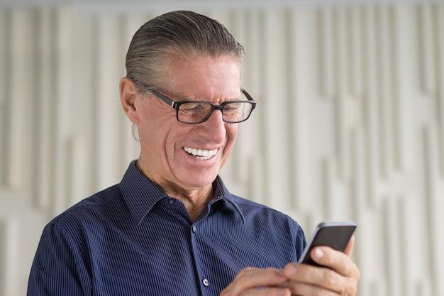 Älterer mann lesetext-meldung am telefon