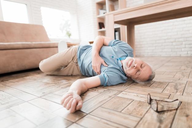 Älterer mann liegt auf dem boden und umklammert herz.
