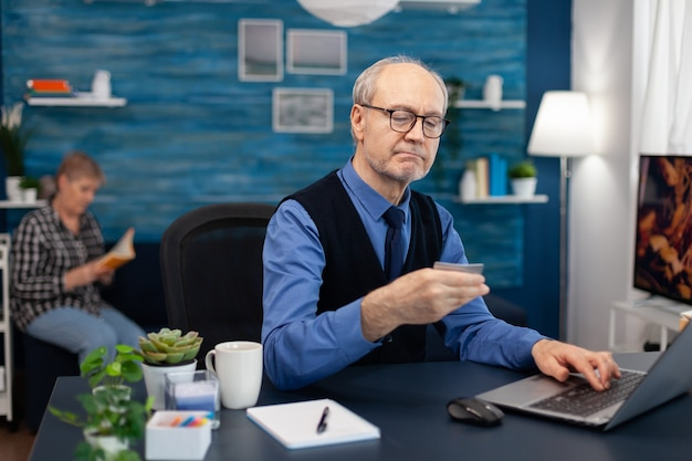Älterer mann liest lebenslauf conde auf kreditkarte mit brille