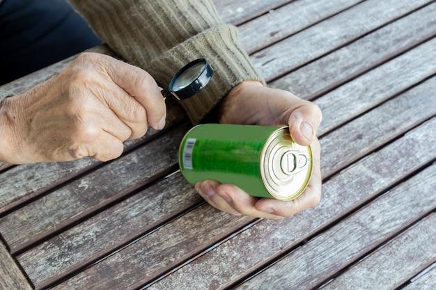 Älterer mann liest zusammensetzung des nahrungsmittelprodukts mit lupe.