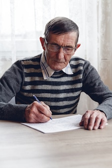 Älterer mann löst sudoku oder ein kreuzworträtsel