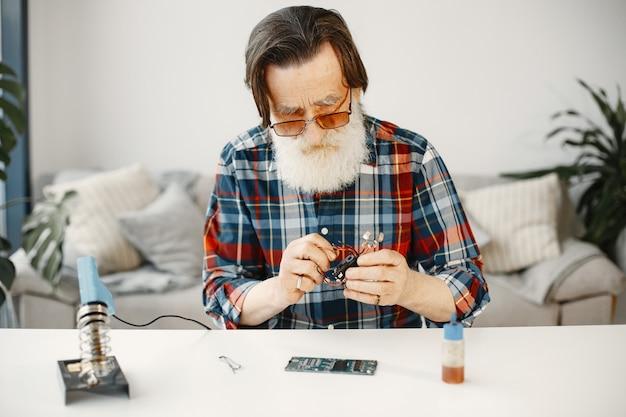 Älterer mann mit ausrüstung zum löten. zuhause arbeiten.