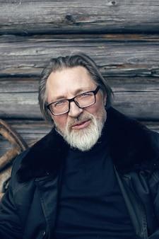 Älterer mann mit bart steht im dorf in der nähe eines holzschuppens in einem schaffellmantel und einer brille