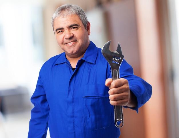 Älterer mann mit blauen overall mit einem schraubenschlüssel