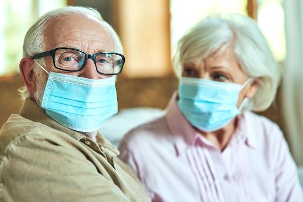 Älterer mann mit brille sitzt neben seiner frau und benutzt masken