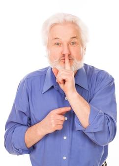 Älterer mann mit dem finger auf die lippen