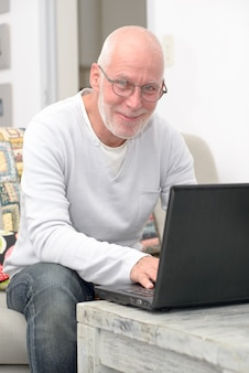 Älterer mann mit dem laptop, der im sofa sitzt