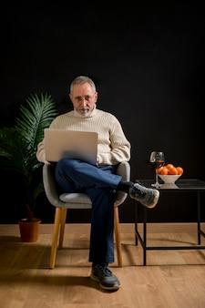 Älterer mann mit dem laptop, der kamera betrachtet