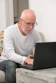Älterer mann mit dem notizbuch, das im sofa sitzt