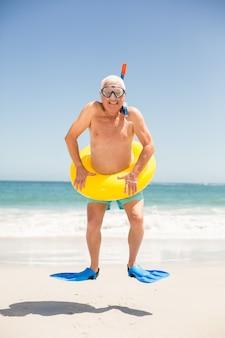 Älterer mann mit dem schwimmring- und flipperspringen