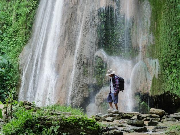 Älterer mann mit den rucksäcken, die am wasserfall gehen. abenteuer, reisen, tourismus-konzept.