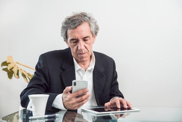 Älterer mann mit der digitalen tablette, die handy betrachtet