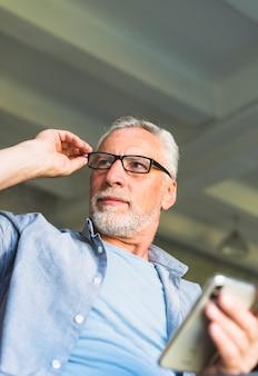 Älterer mann mit der hand auf den brillen, die handy halten
