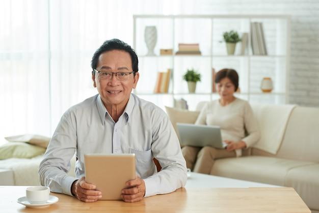 Älterer mann mit digitaler tablette