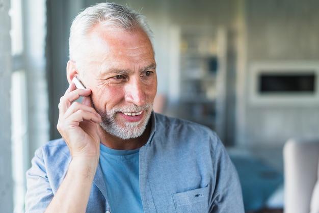 Älterer mann mit drahtlosem bluetooth kopfhörer