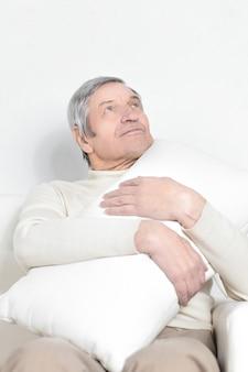 Älterer mann mit einem bequemen kissen. isoliert auf weiß