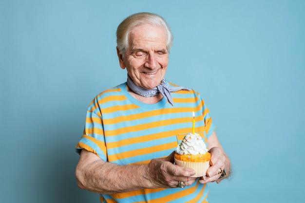 Älterer mann mit einem geburtstagskuchen