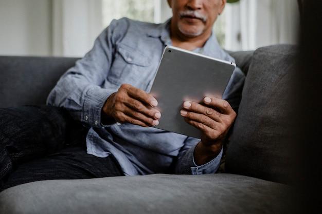 Älterer mann mit einem tablet auf einer couch